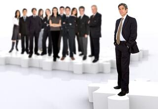 business leadership and teamwork with a businessman in front of a businessteam all standing on puzzle pieces.jpeg
